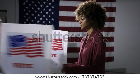MS Young mixed-race woman ready to vote with blurred voting booth in foreground, being removed. Symbol of disenfranchisement with US flag backdrop #1737374753