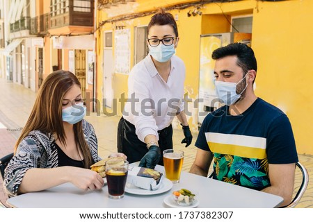 Clients with masks on the terrace of a bar in Spain attended by a waiter with gloves and masks. Social distancing #1737382307