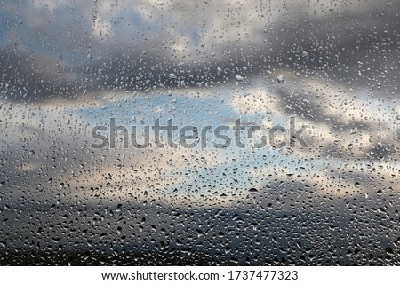 Raindrops on the window glass on blurred background of sky with storm clouds. Beautiful water drops, rainy weather