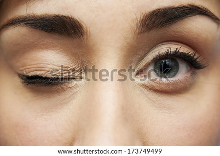 young pretty woman with closed one eye