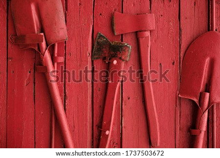 Red fire shield. Axes and shovels on a red background