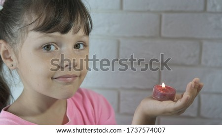 Happy child with candles. Little girl holds a burning candle in her hand. #1737574007