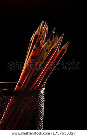 graphite pencils for drawing and writing lined inside black little basket oon the black background #1737633329