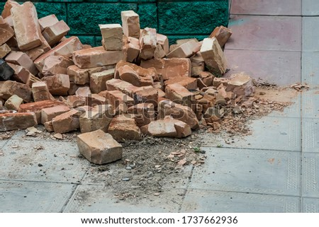 Bricks are on the pavement. Debris on the road. Unused bricks after construction. Broken bricks. Waste bricks. Garbage remained after construction. Texture of broken brick blocks #1737662936