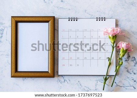 Carnation flower on blank picture frame and calendar on marble background, Valentine's Day, Mother's Day or Birthday background