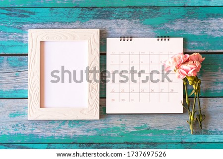 Carnation flower on blank picture frame and calendar on wood background, Valentine's Day, Mother's Day or Birthday background