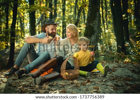 Happy family of three lying in the grass in autumn. A young family with small child having picnic in autumn nature at sunset. The lights of a sun. Happy family in the park evening light