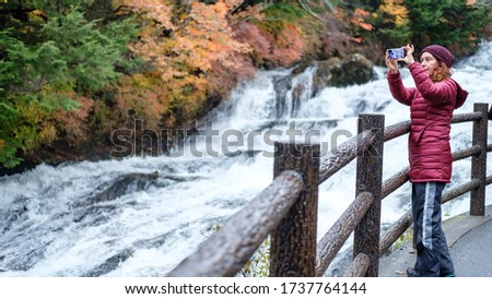 A woman is taking a photo with her smartphone next to a flowing river at autumn, Ryuzu Falls, Nikko National Park, Japan.