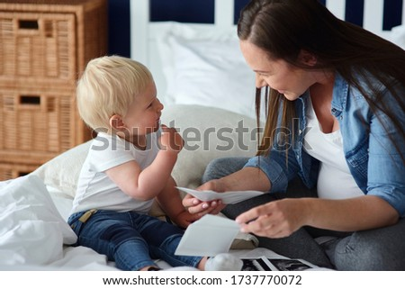 Curious toddler watching pictures of his future brother or sister