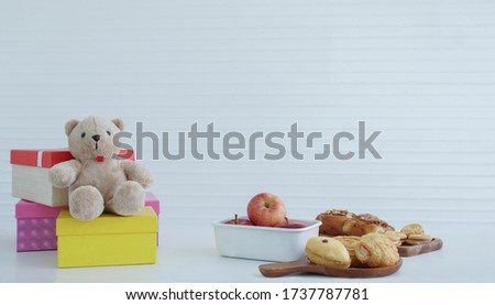 Colorful gift boxes placed with a teddy bear Red apples in a white apple tray, bake bread, cream cookies placed on the table, white background #1737787781