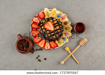 a top view pancakes along with fresh fruits and chocolate on the grey floor #1737895067
