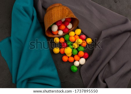 a top view multicolored candies sweet yummy inside brown pot on the grey tissue #1737895550