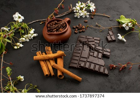 a top view cinnamon chocolate coffee along with white flowers on the dark floor #1737897374