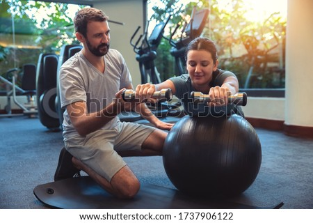 Personal trainer working with client in gym. Trainer man helping woman with her work out with dumbbells on fitness ball Royalty-Free Stock Photo #1737906122