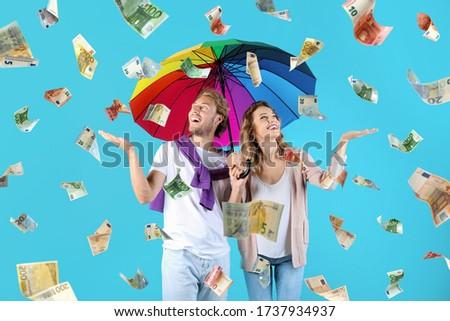 Couple with umbrella under money rain on color background