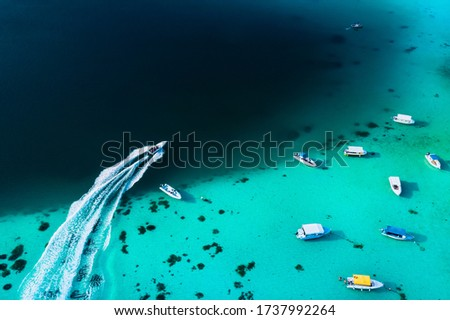Aerial picture of the east coast of Mauritius Island. Beautiful lagoon of Mauritius Island shot from above. Boat sailing in turquoise lagoon