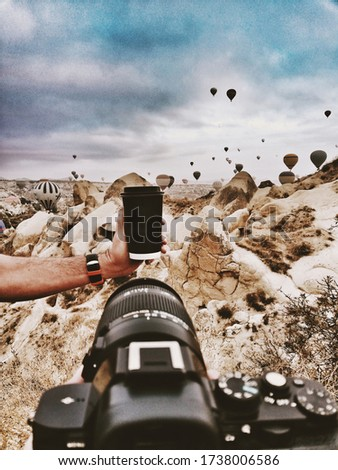 photographer photographing coffee products at the outdoor  with dslr camera.cappadocia air balloon background