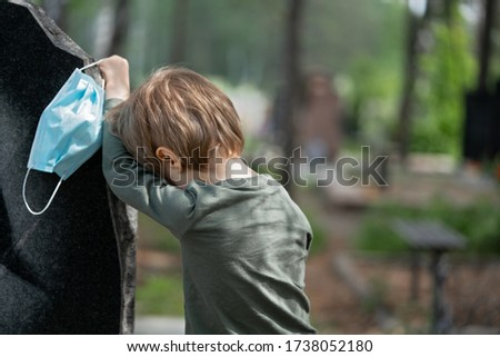 Coronavirus epidemic. Sad boy in medical mask near Headstone. Little boy crying for the loss of his grandfather. Death, cemetery, loss of loved ones due to pandemic. Tragic results of coronavirus Royalty-Free Stock Photo #1738052180
