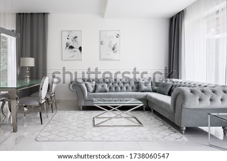 Glamour style living room with white walls and floor, gray quilted sofa, glass coffee table and glass dining table Royalty-Free Stock Photo #1738060547
