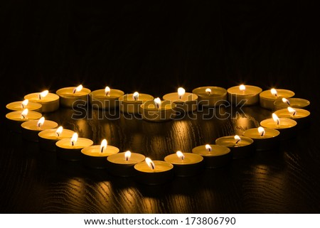 tea lights in the shape of a heart on wood background #173806790