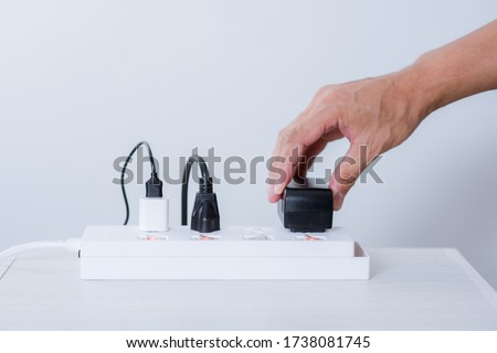 Closeup of a mans hand inserting a plug into electrical power strip. Royalty-Free Stock Photo #1738081745