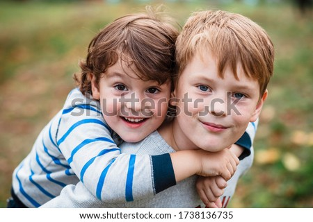 Two happy boys, happy brothers who are smiling happily together. Brothers play outdoors in summer, best friends. Little brother with brother on his back. Two brothers in the woods. Fraternal relations #1738136735