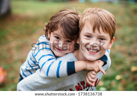 Two happy boys, happy brothers who are smiling happily together. Brothers play outdoors in summer, best friends. Little brother with brother on his back. Two brothers in the woods. Fraternal relations #1738136738