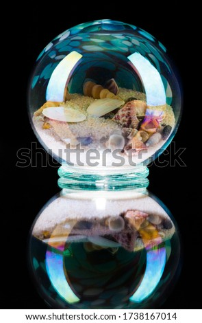 A vertical picture of snails in a crystal ball against a   black background