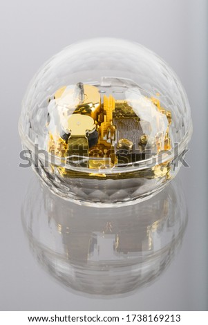 A vertical picture of a golden mechanism in a crystal ball against a grey background