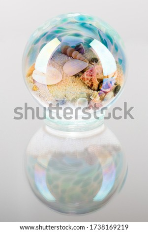 A vertical picture of snails in a crystal ball against a white background