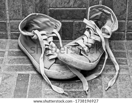 Black and white picture of girl's old worn out dirty high top athletic shoes with long untide laces