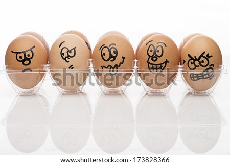 Funny faces on painted on brown eggs over white background