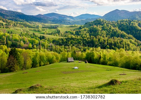 green fields rural landscape. beautiful countryside nature in spring. scenic view of meadow in grass. peaceful nature scenery. hills rolling in to the distant mountain Royalty-Free Stock Photo #1738302782