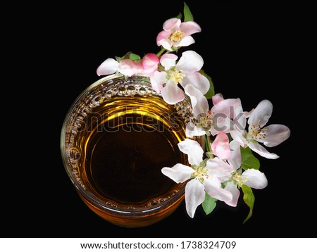 Natural Apple juice in a glass with white apple flowers on a black background closeup, top view. Bright romantic picture with a drink and blooming for the screensaver, wallpaper, cover printing.