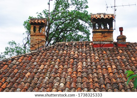 Old orange roof with clay tiles and chimney. View of a part of the tiled roof #1738325333