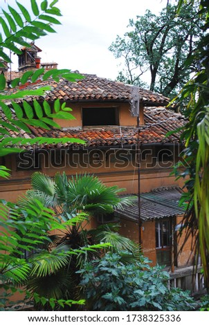 Old house. European building. Orange roof with clay tiles and chimney. Abandoned house with an attic. Grunge texture. Overgrown garden with a palm tree in the yard #1738325336