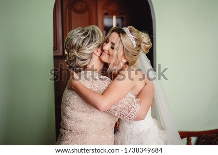 Bride closes her eyes hugging mother tender. Mom congratulates the bride with a marriage and hugs. Happy bride with mother on background wall in home. Bride morning preparation. Film noise #1738349684
