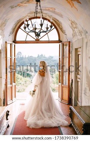 Wedding at an old winery villa in Tuscany, Italy. The bride walks in the interior of the villa, overlooking the garden. #1738390769