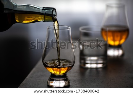 Pouring in tulip-shaped tasting glass Scotch single malt or blended whisky and glas of water Royalty-Free Stock Photo #1738400042