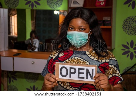 an african small business owner, makeup artist, holding a open sign in her store Royalty-Free Stock Photo #1738402151