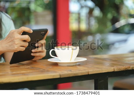 Asian woman shooting picture or take a photo of hot latte coffee with smartphone before drink