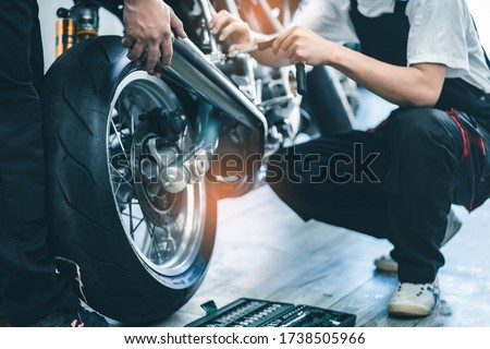 Bike repair. Young man repairing  motobike in garage.mechanic fixing motocycle engine.Serious young man repairing his motorcycle in bike repair shop. #1738505966