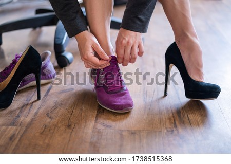 A business woman exchanges high heels for comfortable shoes in the workplace. A close-up of female hands takes off her black shoes and puts on colored sneakers in the office after a long working day. #1738515368
