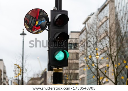 London, England, UK, Green Traffic Light Signal and Traffic Convex Mirror with the Reflection of the red bus