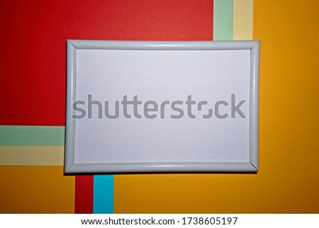 Colorful geometric texture paper pattern in yellow, blue, red, green with a picture frame in white