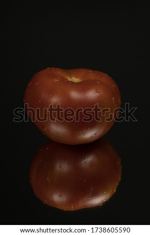Tomato on black reflective studio background. Isolated black shiny mirror background for every concept.
