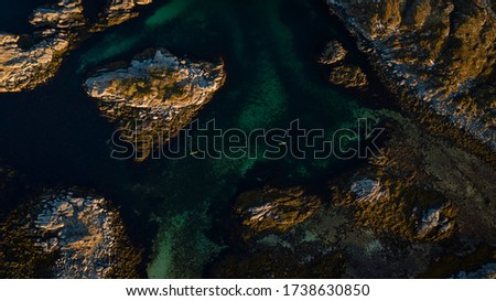 Aerial picture of kayaks between islands. Active summer vacation, north of norway located in lofoten islands.Two people kayaking surrounded beautiful landscape and turquoise sea. picture from distance