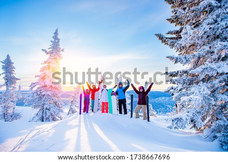 Group of snowboarders and skier dawn with snowboards rejoice snow Light sun in winter forest sunrise. Concept life style, travel.