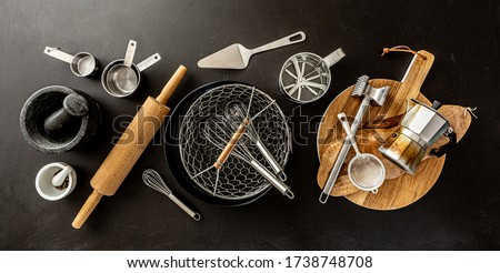 Kitchen utensils (cooking tools) on black chalkboard background - horizontal banner layout. Kitchenware collection captured from above (top view, flat lay). Royalty-Free Stock Photo #1738748708