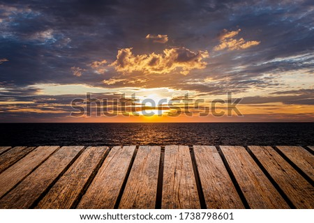 Old wooden table Brown grunge placed separately on a Sea view Sunset and rain clouds background For home decoration